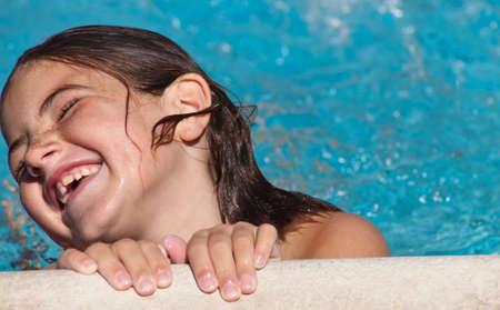 Une étroite une jeune fille rire autour de la piscine. Banque d'images