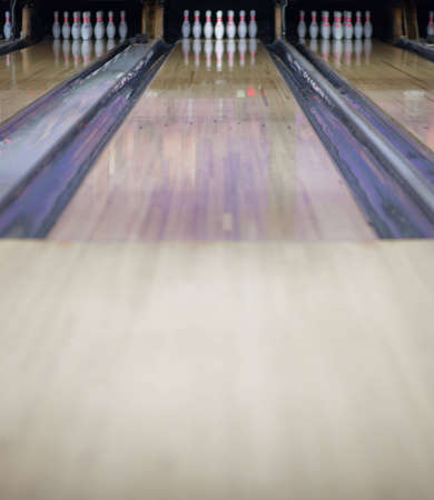 A shot of a bowling lane with all ten pins up.