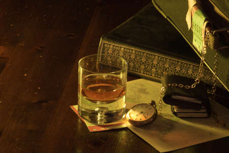 A close up of a travel scene, with luggage, photo album, wallet, pocket watch, map, tickets and a glass of whiskey.