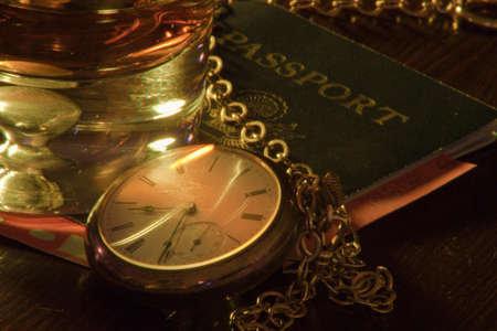 A close up of a pocket watch and low ball glass with whiskey and a passport. photo