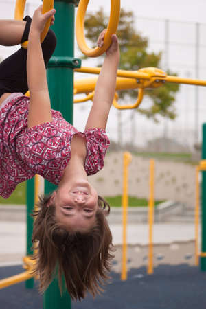 A close up of a young girl hanging up upside down with a big smile. photo