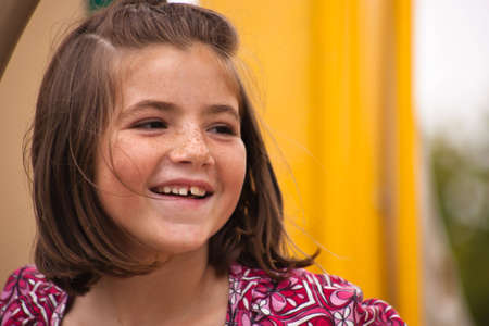 A close up of a young girl with a big smile. photo