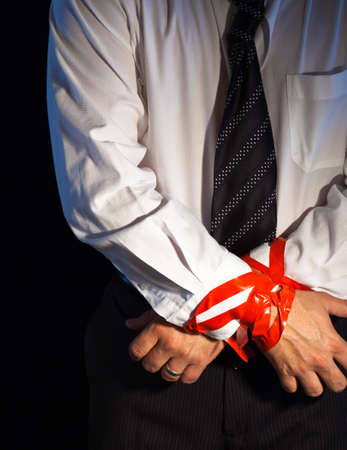 A close up of a man in a suite with his hands tied up with red tape. 版權商用圖片