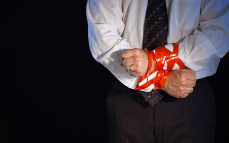 A close up of a man in a suite with his hands tied up with red tape. Stock Photo