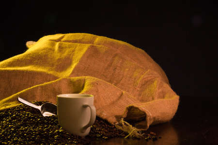 A close up of a burlap coffee bag opened with coffee beans spilling out with a cup of coffee in the foreground. Stock Photo - 8143798