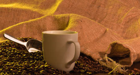A close up of a burlap coffee bag opened with coffee beans spilling out with a cup of coffee in the foreground. Stock Photo - 8143793