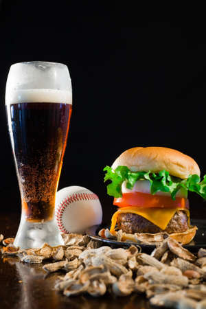 A close up of a big hamburger surrounded with peanuts, beer and a baseball ball. Stock Photo - 8750239