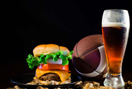 A close up of a big hamburger surrounded with peanuts, beer and a football.