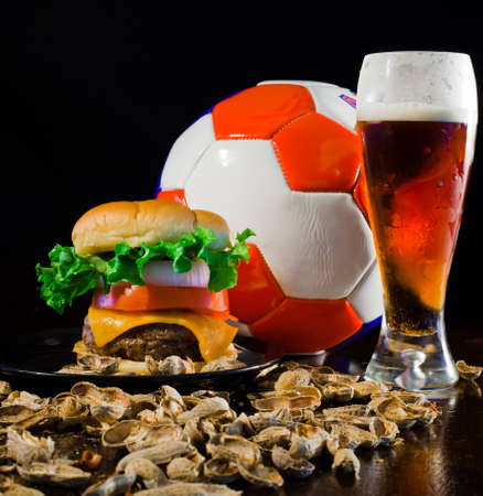 A close up of a big hamburger surrounded with peanuts, beer and a soccer ball. Banque d'images