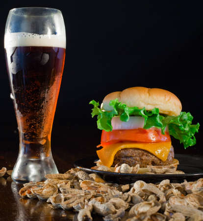 A close up of a big hamburger  and beer surrounded with peanuts. Stock Photo - 8750249