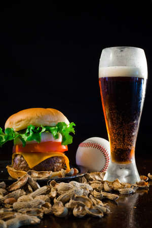 A close up of a big hamburger surrounded with peanuts, beer and a baseball ball. Stock Photo