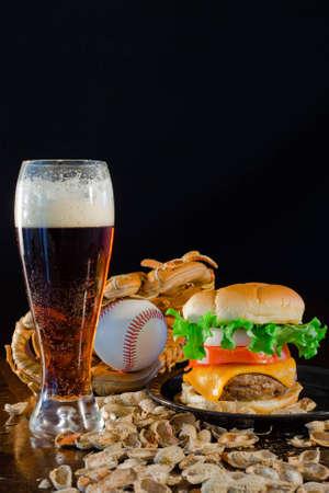 guante de beisbol: A cerca de una hamburguesa big rodeada de man�, cerveza y un guante de b�isbol y la bola.