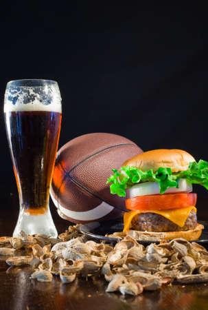A close up of a big hamburger surrounded with peanuts, beer and a baseball ball. Stock Photo - 8750245