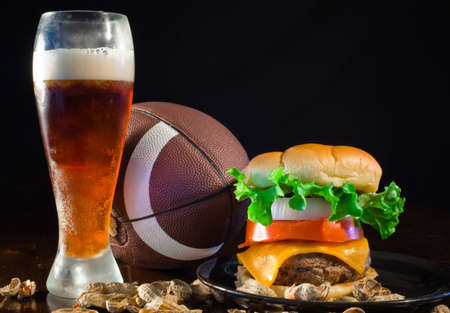 A close up of a big hamburger surrounded with peanuts, beer and a football. Stock Photo - 8750255