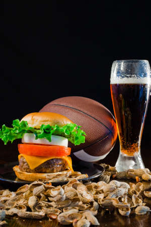 A close up of a big hamburger surrounded with peanuts, beer and a football. Stock Photo - 8750247