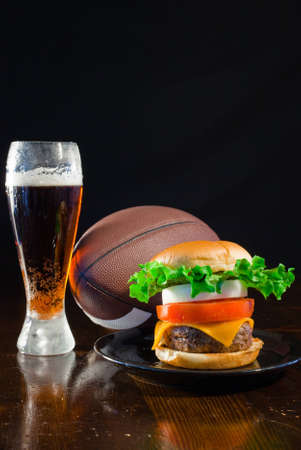sports bar: A close up of a big hamburger on a black plate with a cold amber beer and a football.