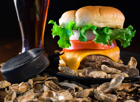 A close up of a big hamburger surrounded with peanuts, beer and a ice hockey puck.