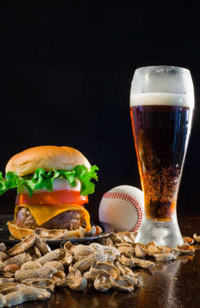 A close up of a big hamburger surrounded with peanuts, beer and a baseball ball. Banque d'images