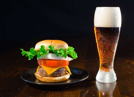 A close up of a big hamburger on a black plate with a cold amber beer. Stock Photo