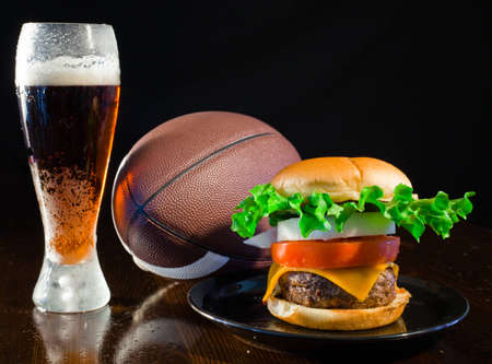 A close up of a big hamburger on a black plate with a cold amber beer and a football. Stock Photo - 8750273