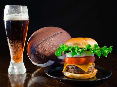 A close up van een grote hamburger op een zwarte plaat met een koud amber bier en een voetbal. Stockfoto