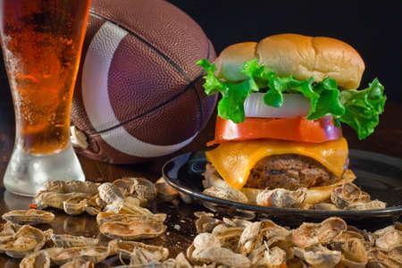 Een close up van een grote hamburger omringd met pinda's, bier en een voetbal. Stockfoto