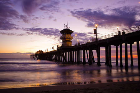 A shot looking out to Huntington Beach Pier, with a purple  sky sunset. Stock Photo