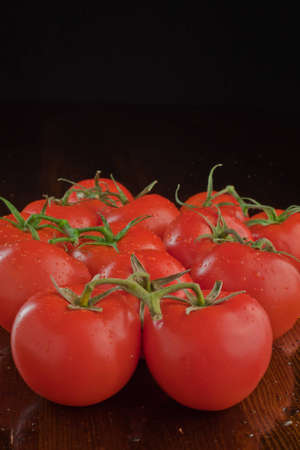 A close up of a bunch of tomatoes stacked up with a black background.