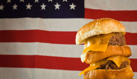 A close up of a five patty cheese burger with a US flag in the background. Stock Photo - 9857320