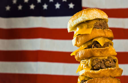 A close up of a five patty cheese burger with a US flag in the background. Stock Photo - 9857321