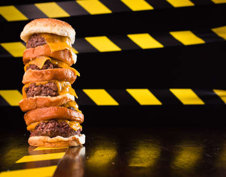 A close up of a five patty cheese burger, with caution lines in the background. Stock Photo - 9857318