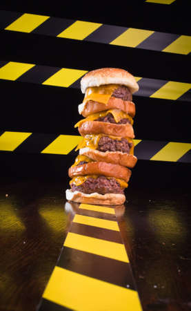A close up of a five patty cheese burger, with caution lines in the background. Stock Photo - 9857311