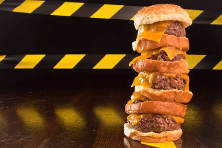 A close up of a five patty cheese burger, with caution lines in the background. Stock Photo - 9857329