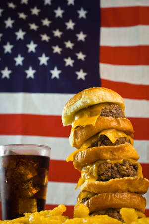 A close up of a five patty cheese burger, fries, iced soda and US flag in the background. photo