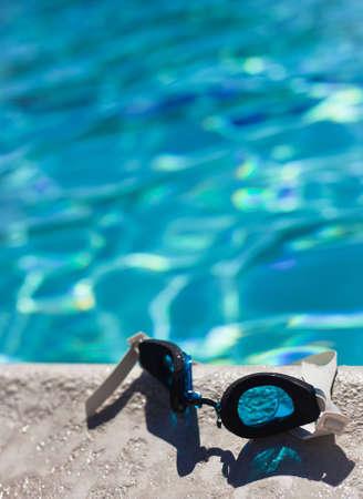 swim goggles: A cerca de un par de gafas de nataci�n que pone en el borde de la piscina. Foto de archivo