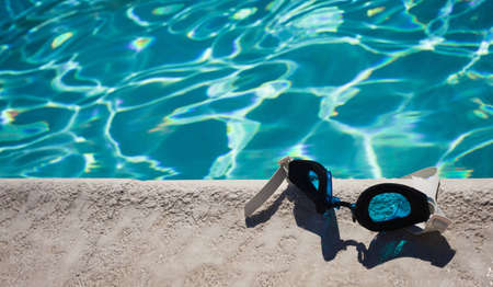 A close up of a pair of swim goggles laying on the edge of the pool.