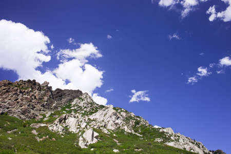 A shot looking up to a rocky green mountain with a blue cloudy sky. Banco de Imagens