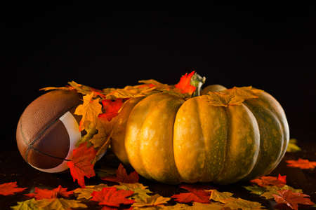 A studio shot of a pumpkin and a football with fall leaves.