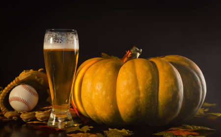 A studio shot of a pumpkin and a baseball glove, ball and a tall beer.