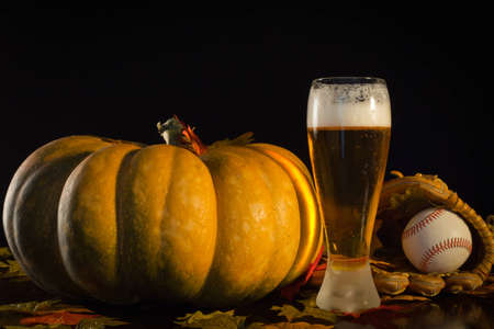 A studio shot of a pumpkin and a baseball glove, ball and a tall beer. Stock Photo - 10828433