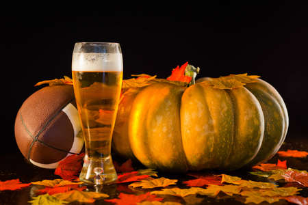 A studio shot of a pumpkin, football, leaves and a tall cold beer. Stock Photo