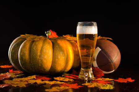 A studio shot of a pumpkin, football, leaves and a tall cold beer. Banque d'images