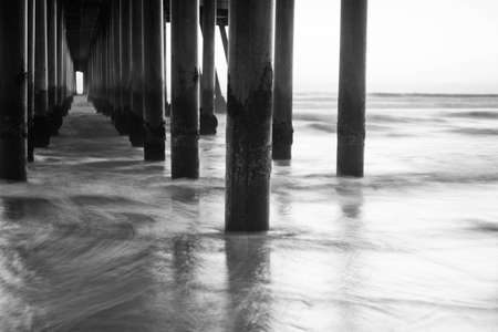 A shot looking out under a pier at all the columns during sunset. Standard-Bild