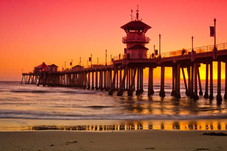 A wide shot of the Huntington Beach Pier during a bright red and orange sunset. Stock Photo