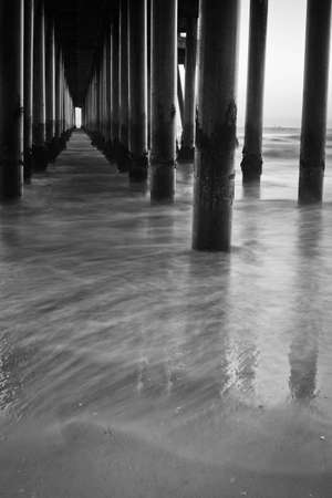 A shot looking out under a pier at all the columns during sunset. Stock Photo