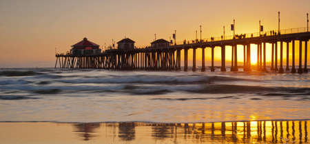 A wide shot of the Huntington Beach Pier during a bright orange sunset.