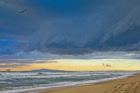 A wide shot looking out from Huntington Beach north to Long Beach and the Palos Verdes Peninsula during a windy stormy February day. photo