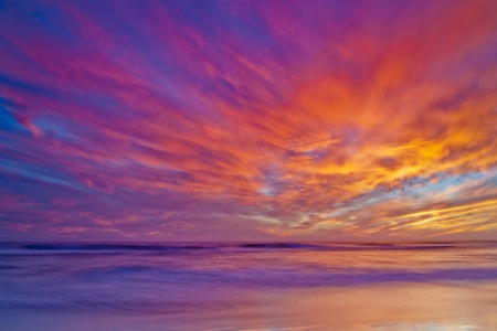 Široký záběr s výhledem na Tichý oceán při západu slunce v Huntington Beach.