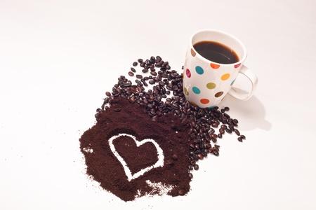 coffee grounds: A close up of a Polka Dot coffee cup, coffee beans, and coffee grounds with a heart shape in the grounds all with a white background.