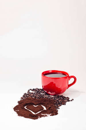 coffee grounds: A close up of a red coffee cup, coffee beans, and coffee grounds with a heart shape in the grounds all with a white background.